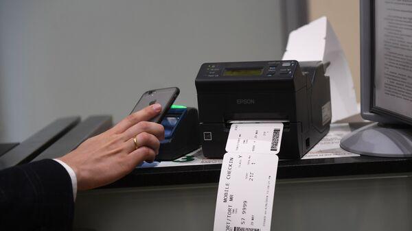 Пассажир сканирует и распечатывает посадочный талон в аэропорту