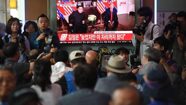 Люди смотрят за встречей Трампа и Ким Чен Ына по ТВ. 12.06.2018