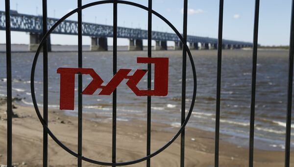 Логотип РЖД на фоне железнодорожного моста