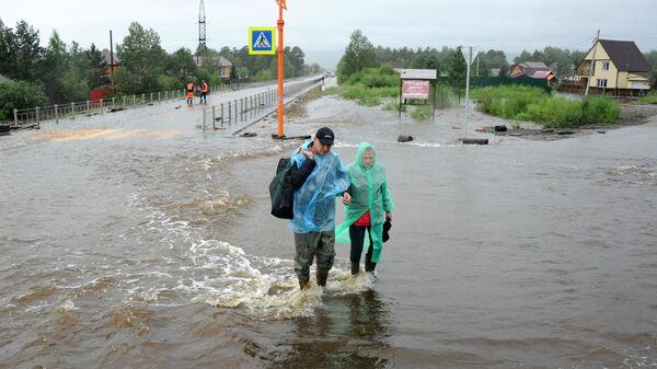 Местные жители на затопленной в результате паводка улице в Чите