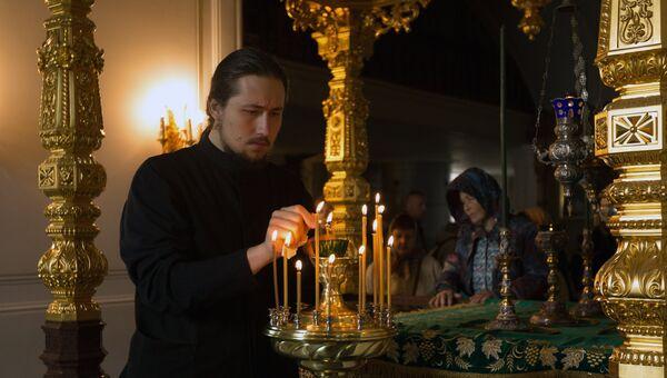 Монах зажигает лампады у раки с мощами святых Сергия и Германа в день церковного празднования памяти валаамских чудотворцев преподобных Сергия и Германа