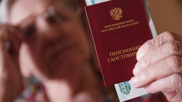 Женщина держит пенсионное удостоверение. Архивное фото