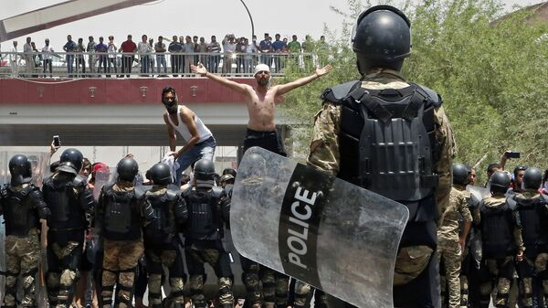Иракская полиция и демонстранты возле здания администрации провинции Басра на юге Ирака. 15 июля 2018 года