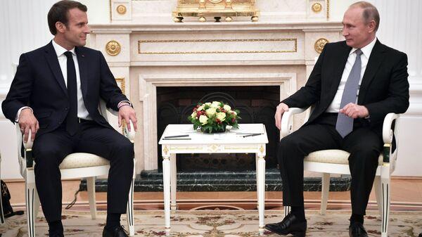 Президент РФ Владимир Путин и президент Франции Эммануэль Макрон (слева) во время встречи. Архивное фото