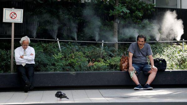 Мужчины отдыхают возле распрыскивателя воды в одном из парков Токио. 17 июля 2018