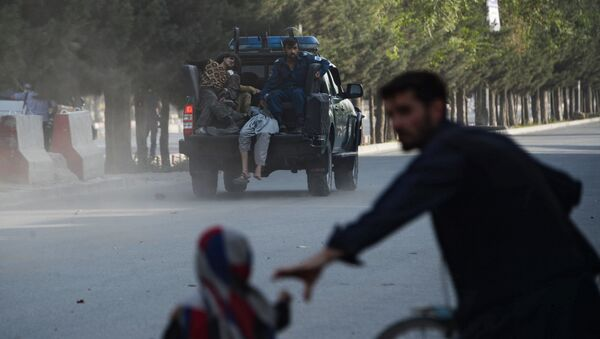 Полиция Афганистана увозит раненых с места взрыва в аэропорту Кабула. 22 июля 2018