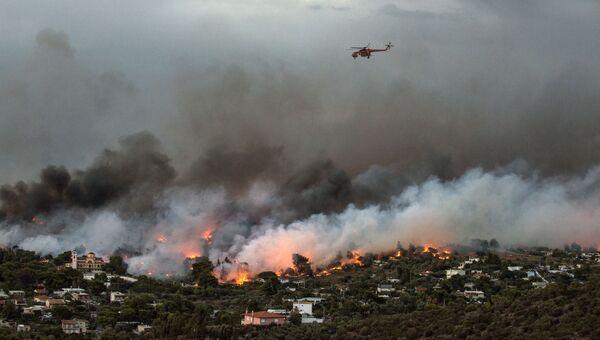 Пожарный вертолет пролетает над лесным пожаром в городе Рафина около Афин, Греция. 23 июля 2018 года