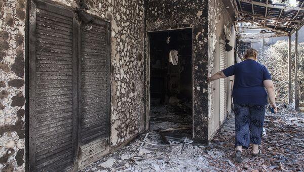 Женщина у своего дома, пострадавшего в результате лесных пожаров, в поселении Мати в Греции. 25 июля 2018