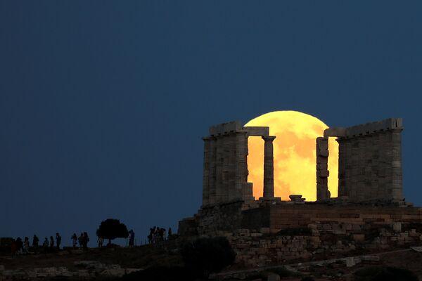 Люди наблюдают за восходом полной луны за храмом Посейдона перед лунным затмением недалеко от Афин, Греция. 27 июля 2018