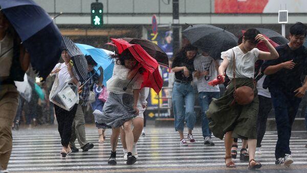 Жители Токио с зонтами спасаются от обрушившегося на город  тайфуна Джондари. 28 июля 2018