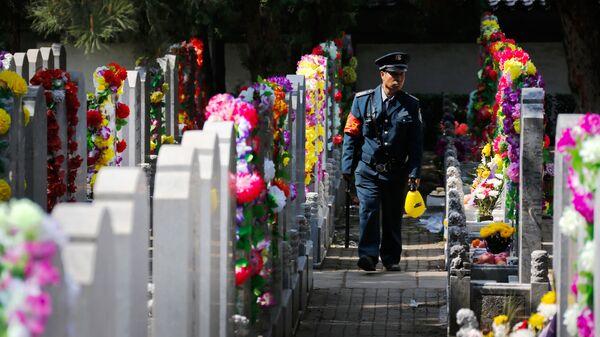 Сотрудник службы охраны на кладбище в Китае. Архивное фото