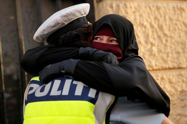 Женщина обнимает полицейского во время демонстрации против запрета на ношение паранджи в Дании. 1 августа 2018 года.