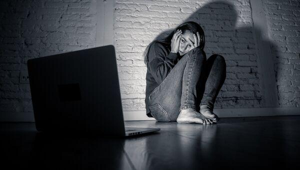 Расстроенная девушка сидит около ноутбука
