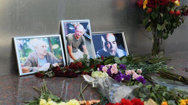 Цветы у фотографий погибших в Центральноафриканской Республике российских журналистов возле Дома журналистов в Москве