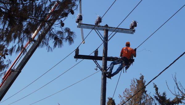 Рабочие меняют провода на линиях электропередачи