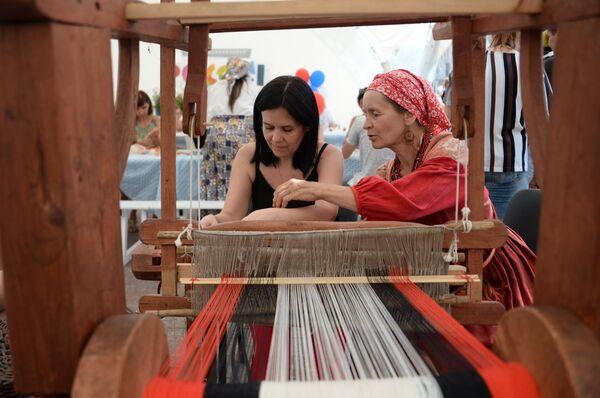 Посетители во время мастер-класса по ткацкому делу на фестивале Многонациональная Россия в Москве