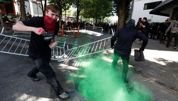 Протестующие бегут от полицейского снаряда во время митинга в Портленде, США. 4 августа 2018
