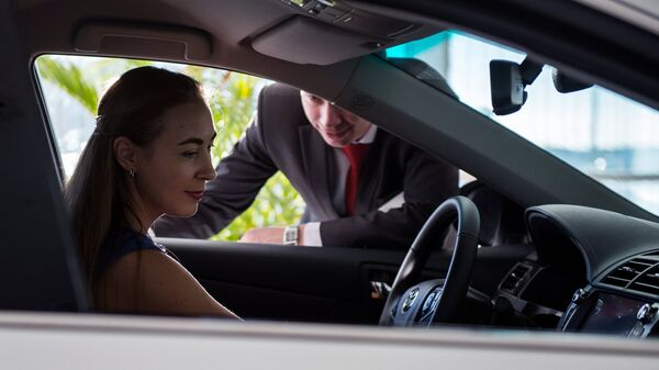 Девушка выбирает автомобиль в автосалоне