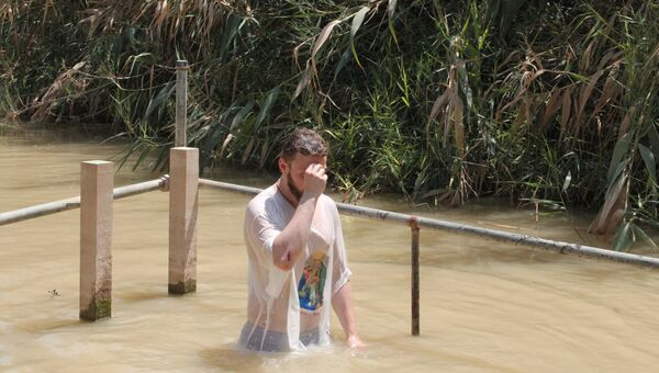 Верующие купаются в реке Иордан