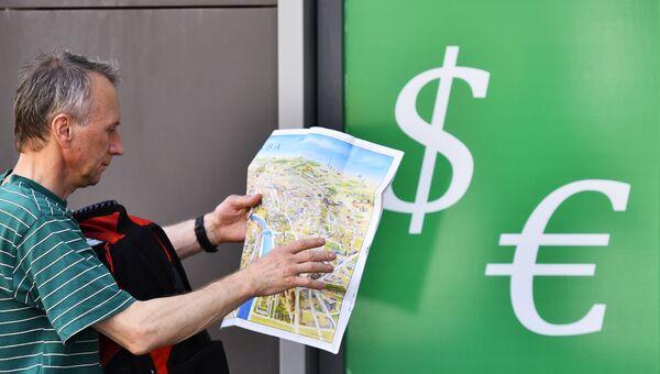 Мужчина у пункта обмена валюты. Архивное фото