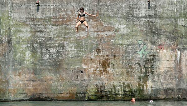Девушка прыгает в воду в жаркий летний день из старого бункера в районе Нойхаузен-ам-Райнфалль, Швейцария. 6 августа 2018 года