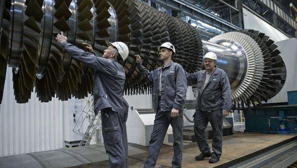 Рабочие ООО Сименс технологии газовых турбин осматривают ротор с лопатками в цехе по восстановлению лопаток газовых турбин
