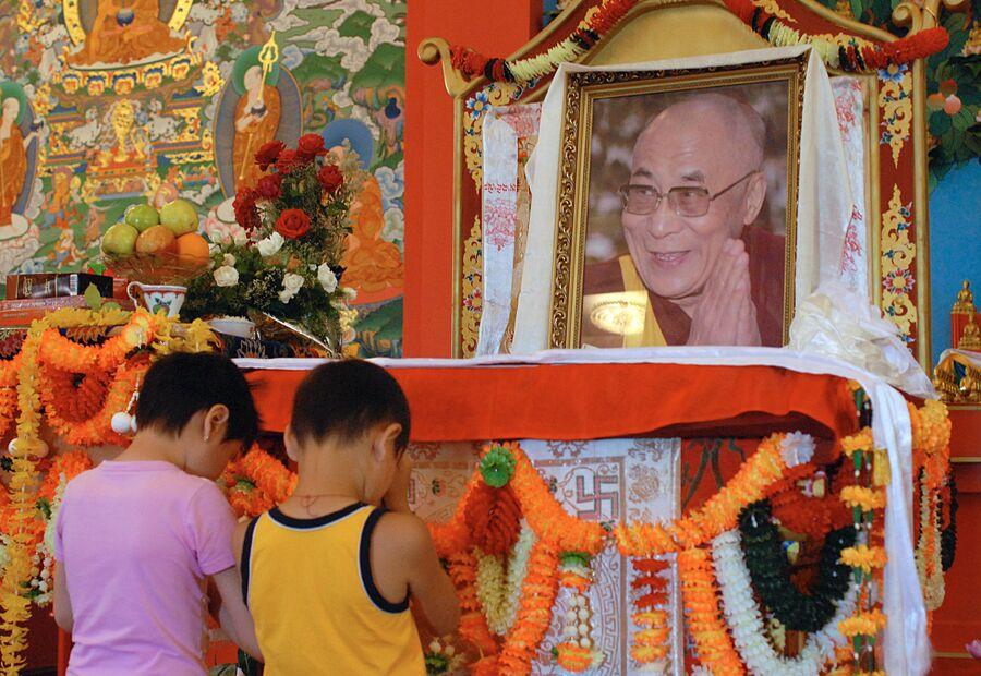 Дети молятся у портрета Его Святейшества Далай-ламы XIV во время молебна-поздравления в Центральном калмыцком хуруле Золотая обитель Будды Шакьямуни