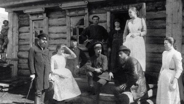 Сестры милосердия стоят на крыльце дома с местными жителями. Санитарный поезд в селе Нарукеево, голодный год, 1891-1892 г. г.