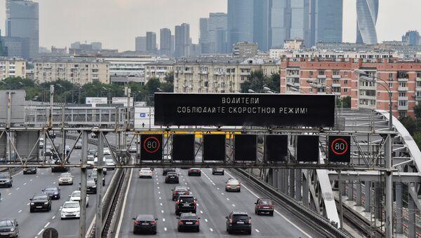 Предупреждение о соблюдении скоростного режима на Андреевском мосту. На дальнем плане: небоскребы делового цетра Москва-сити