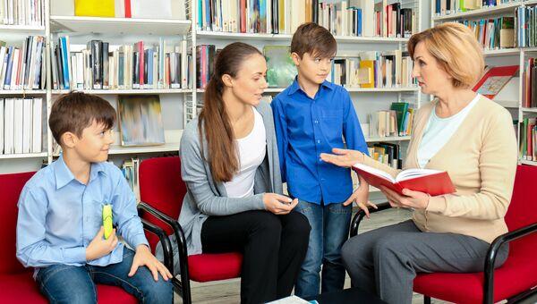 Мама с детьми общаются с учителем. Архивное фото