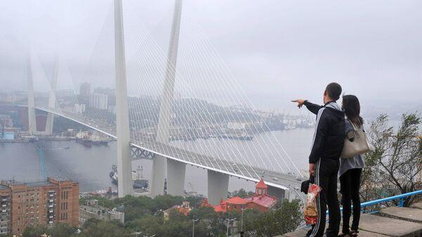 Туристы любуются мостом через бухту Золотой Рог во Владивостоке. Архивное фото