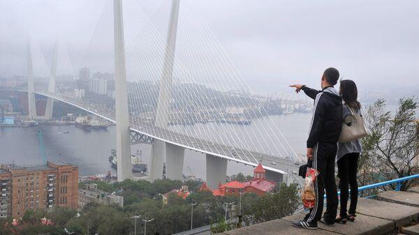 Туристы любуются мостом через бухту Золотой Рог во Владивостоке
