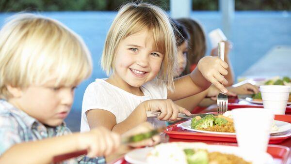 Учащиеся начальной школы во время обеда в столовой