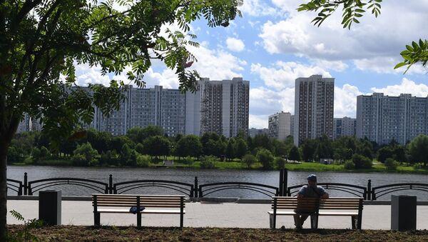 Мужчина сидит на лавочке на набережной Москвы-реки на территории парка 850-летия Москвы в районе Марьино. Архивное фото