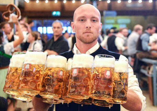 Официант разносит бокалы с пивом на открытии традиционного пивного фестиваля Октоберфест в Мюнхене