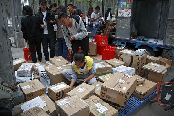 Сотрудники службы доставки сортируют посылки возле офисного здания в Пекине