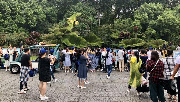Китайские туристы фотографируются у озера Сиху, Ханчжоу, Китай