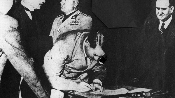 Рейхсканцлер Германии Адольф Гитлер подписывает Мюнхенское соглашение 1938 года о разделе Чехословакии