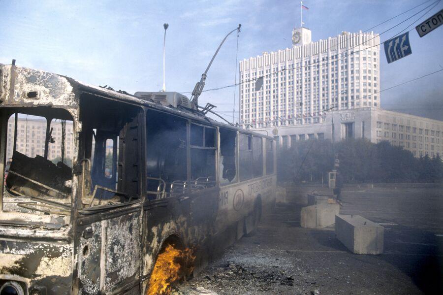 Обгорелый троллейбус у здания Дома Советов Российской Федерации во время интенсивного танкового обстрела