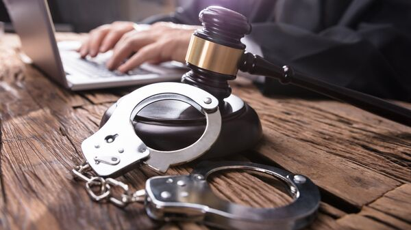 Молоток и наручники на столе у судьи. Архивное фото