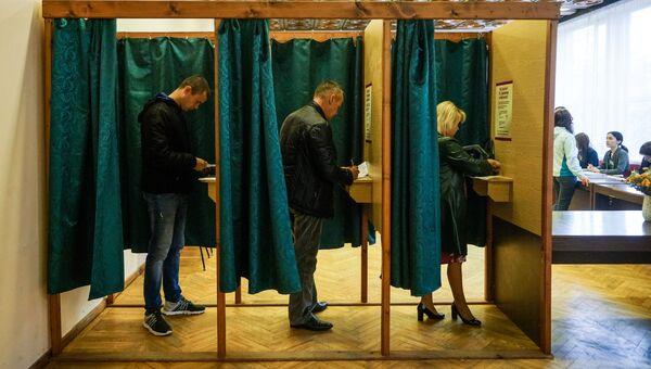 Избиратели голосуют на избирательном участке в Огре во время парламентских выборов в 13-й Сейм Латвии. 6 октября 2018