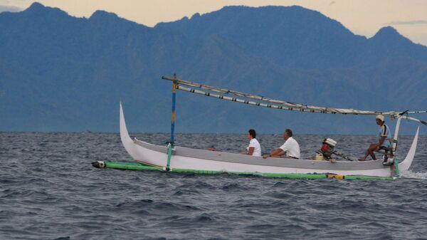 Туристы катаются на лодке у побережья острова Бали