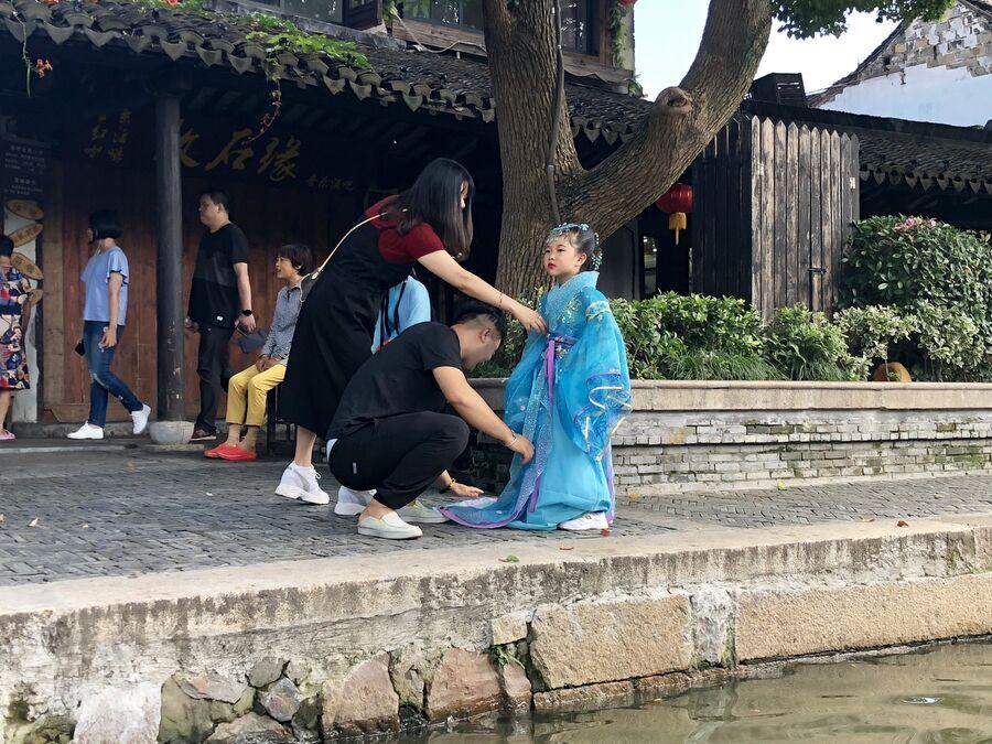 Девочку готовят к фотосессии в традиционном костюме, Ситан, Китай