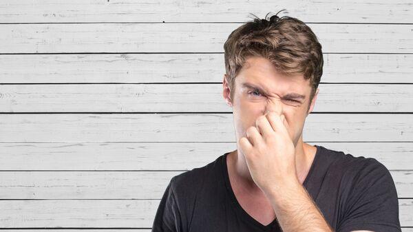 Мужчина зажимает нос
