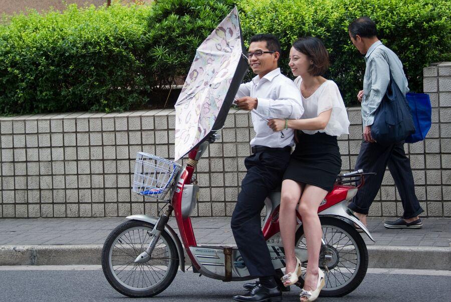 Молодые люди сидят на мопеде. Китай