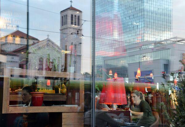 Собор св. Иосифа и небоскреб отражаются в витрине кафе города Сараево