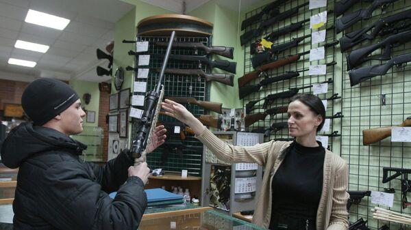 Продавец консультирует покупателя в оружейном магазине
