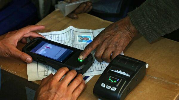 Мужчина во время регистрации перед голосованием на одном из избирательных участков Кабула