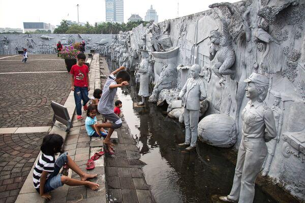 Дети играют во дворе Национального памятника Монас на площади Мердека в Джакарте
