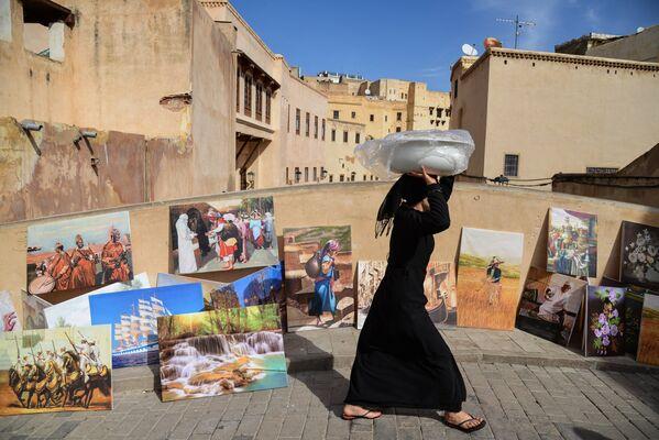 Женщина идет по мосту в городе Фес